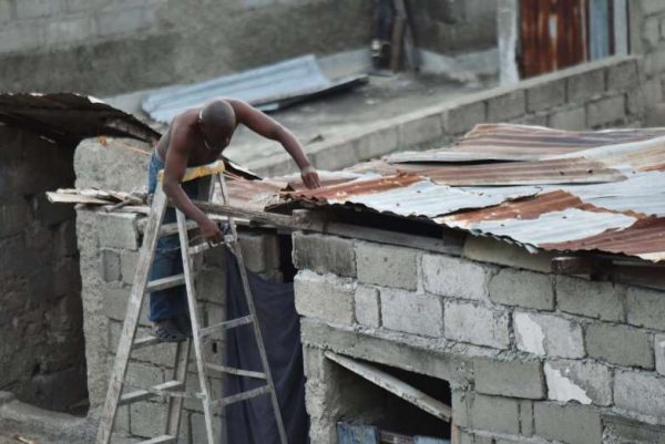 A man repairs a part of his roof in preparation for the arrival of Hurricane Irma on Sept. 6, 2017, in Lauriers neighborhood of Cap-Haitien, 240 km from Port-au-Prince