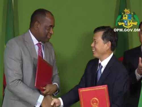 Prime Minister Roosevelt Skerrit (left) and China's ambassador LU Kun shake hands after signing MOUs